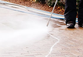 man pressure washing a sidewalk